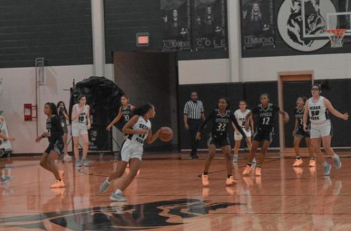 Point guard Gisella Maul dribbles and runs towards the net while playing against members of Cibolo Steel. Although the Nov. 13 game ended in a loss 54 - 56, the girl's varsity team proceeded to win every game in the season afterwards. Maul owes the team's victories to their teamwork and coaching.