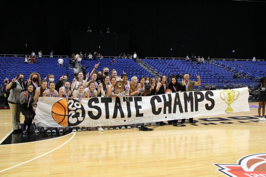 Smiling together, the Lady Timberwolves hold the 5A Girls Basketball State Champion trophy on March 10. After a neck and neck game, the team won 46-39 against Frisco Liberty.