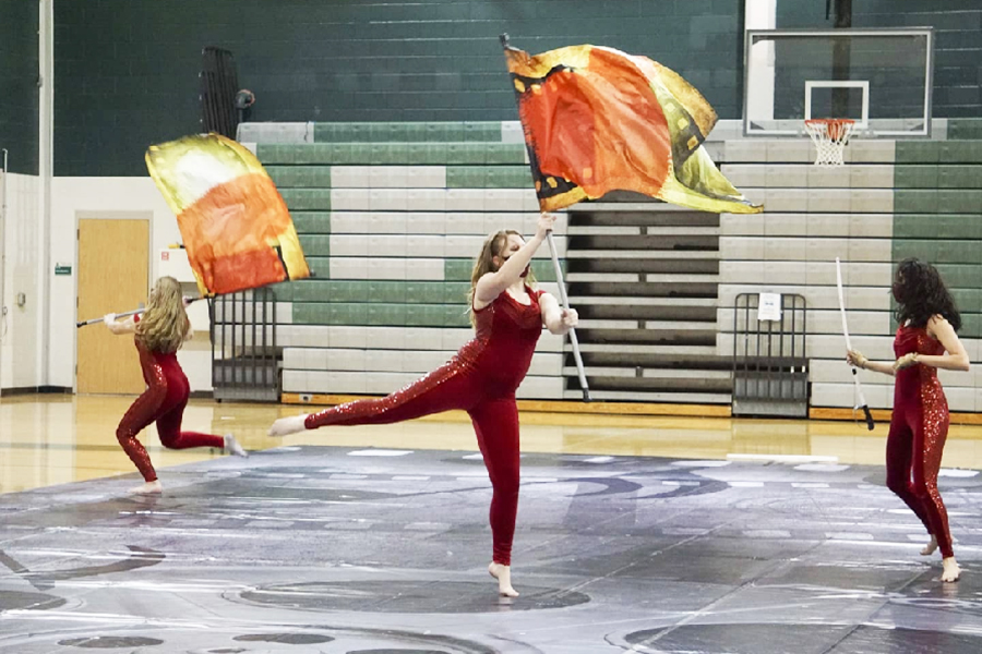 Holding+their+flags%2C+the+color+guard+performs+in+the+gym.+Although+the+varsity+team+did+not+make+it+to+finals+this+year%2C+according+to+senior+color+guard+member+Bolt+Gonzalez%2C+the+color+guard+was+able+to+overcome+many+challenges%2C+including+virtual+competitions.+%0A%E2%80%9CWe+are+all+%5Bin%5D+guard+to+learn+new+things+and+be+challenged+so+we+are+happy+with+the+progress+we+have+made+this+year%2C%E2%80%9D+Gonzalez+said.+%E2%80%9CIt+sucks+a+little+not+having+in-person+competitions+and+performing+in+a+mask+is+difficult+at+times+but+we+can+still+be+together+and%2C+to+me%2C+that%E2%80%99s+what+counts.%E2%80%9D%C2%A0