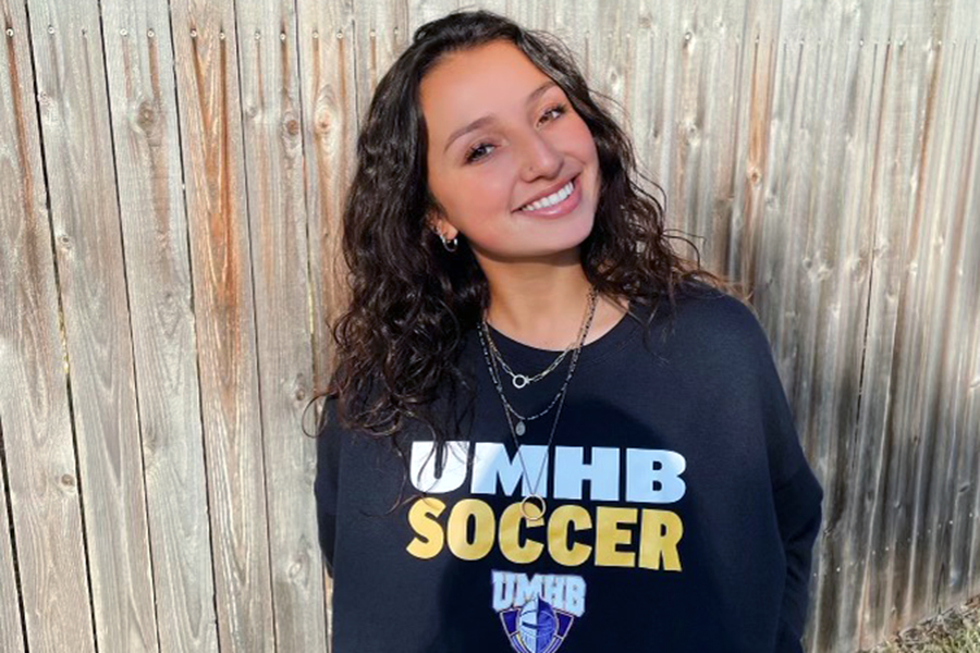"""Smiling at the camera, senior Breland Mungia shows off her University of Mary Hardin-Baylor soccer shirt.  When collegiate offers began rolling in during the fall of her junior year, although Mungia was excited, she knew she wanted to stay in Texas to continue her education. The University of Mary Hardin-Baylor became the perfect choice and she officially committed to play soccer.  """"I am very much a homebody and being on that campus made me feel comfortable and at home,"""" Mungia said. """"The quality of their athletic facilities was also very appealing and everyone I met on campus was so welcoming."""