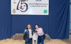 """Holding her lamb, senior FFA president Skye Lindholm poses at the annual Williamson County Livestock show. Lindholm joined FFA during her freshman year and has held multiple officer positions and participated in many competitions throughout high school. """"Being a member of FFA has taught me how to be a responsible, contributing member of society,"""" Lindholm said. """"During my time in FFA, I was fortunate enough to be under our advisors who helped me grow and [become] better as a person."""""""