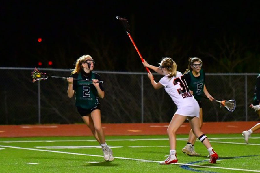 "Sophomore Kamryn Kramer skillfully keeps the ball away from her opponent. ""[The hardest part of] lacrosse is defense,"" Kramer said. ""Also having the endurance to run back and forth on midfield especially if you are playing a hard team."""