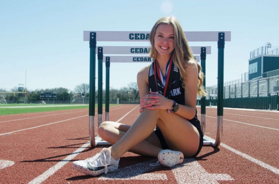 Next to hurdles, senior Erika Arthur poses during a team photoshoot. Arthurs main events, are the hurdles as well as distance events. I had the best time running with my teammates, Arthur said. It makes your accomplishments that much better when you have people to support you.