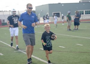 """Running with a ball clutched in his arm, Kason Fuller, a member of the nonprofit organization Cheyanna's Champions 4 Children (CC4C), participates in the varsity football teams after school practice. Fuller, who was diagnosed with PANDAS when he was five, is an outdoor enthusiast with a newfound interest for football. Me and my dad usually practice football outside,"""" Fuller said. """"We usually catch the ball, but sometimes we act out players."""