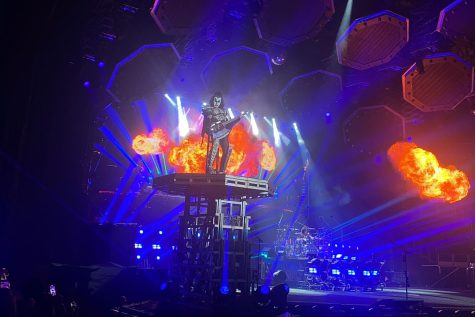Playing the guitar, Gene Simmons performs as flames shoot out behind him. This is just one of the many times he was lifted on the platform. The 72-year-old musician created the band KISS in 1972 with lead singer Paul Stanley.