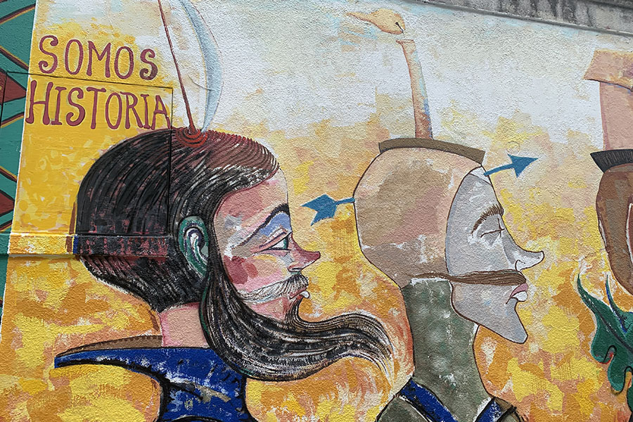 """Depicted above is the current mural outside of the Mexic-Arte Museum entitled Somos Historia. The artist, Luis Abreux earned his Master's degree in Fine Art, specializing in Painting, from the San Alejandro Art Academy in Havana, Cuba and has lived in Austin since 2005. """"My mural is a historical portrait,"""" Abreux said. """"The satirical style in my work reinforces the theatrics of life and how the most valuable things are relative-like the lives exchanged for gold 500 years ago."""""""